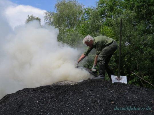 Nach dem Anheizen wird der Mittelschacht mit einem Deckel verschlossen. Bei wenig Luftzufuhr schwelt das Holz statt zu brennen